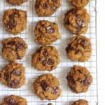 Overhead shot of pumpkin chocolate chunk cookies on a cooling rack on white background.