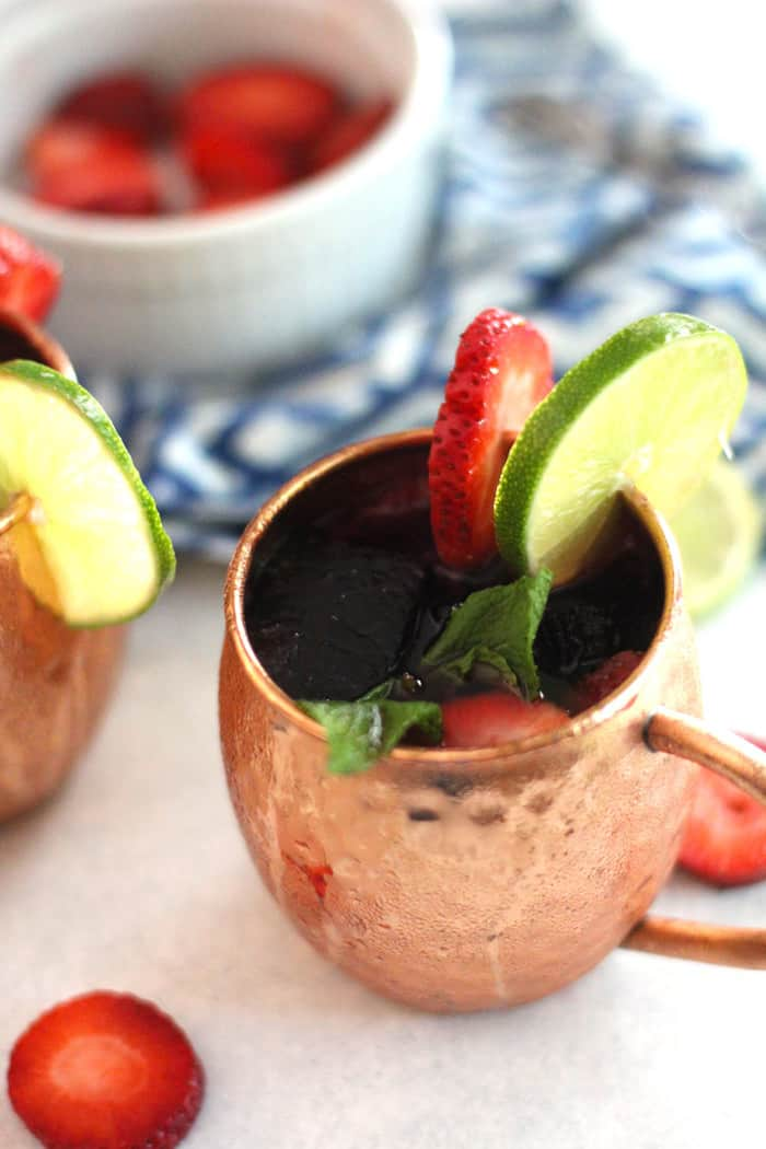 Strawberry Mexican Mules are a spin on the traditional mule recipe. Muddle some strawberries and mint, and use Tequila instead of Vodka. Use fruit flavored ice cubes for a sweeter cocktail! | suebeehomemaker.com