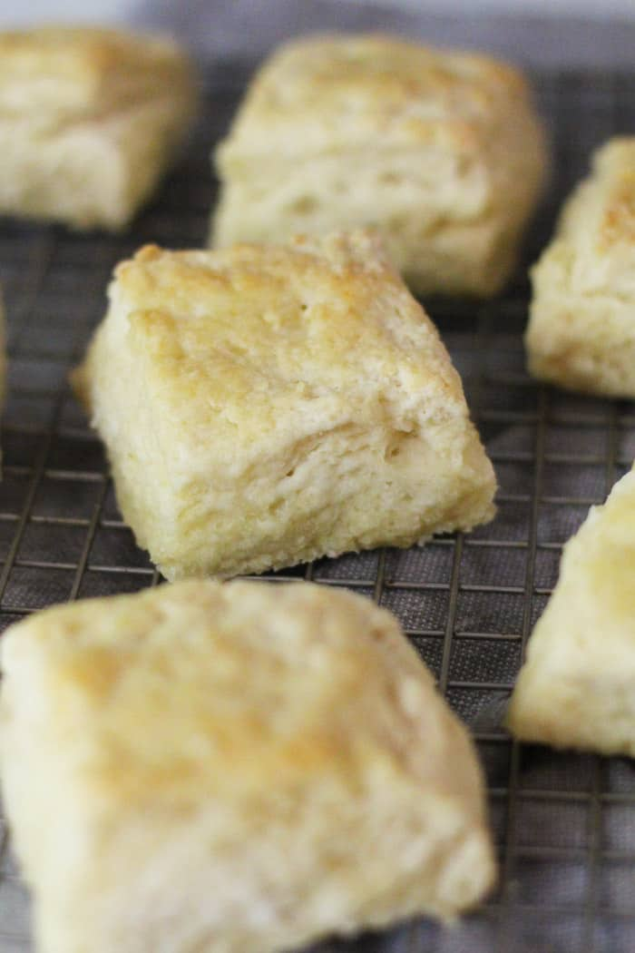 A side shot of a few buttermilk biscuits on a wire cooling rack, with the middle biscuit in focus and the others out of focus.