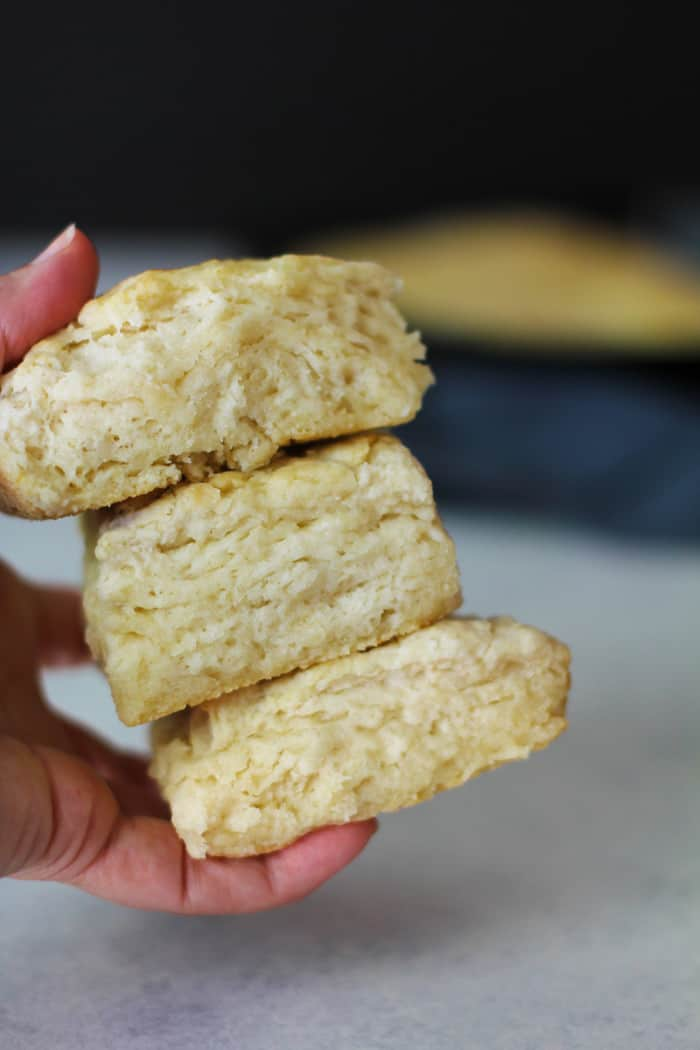 Side view of my hand holding three thick buttermilk biscuits, with the pan in the background over a white background.