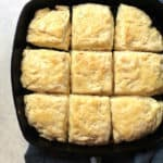 Overhead shot of a square cast iron skillet with nine buttermilk biscuits, coated with butter, all on a blue napkin over a white background.