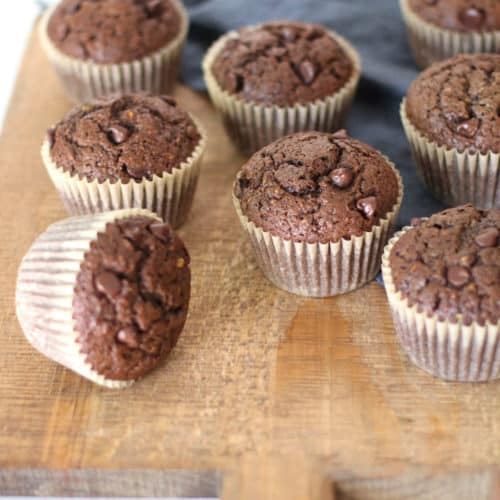 Overhead shot of chocolate zucchini muffins on a wooden board, with a blue napkin.