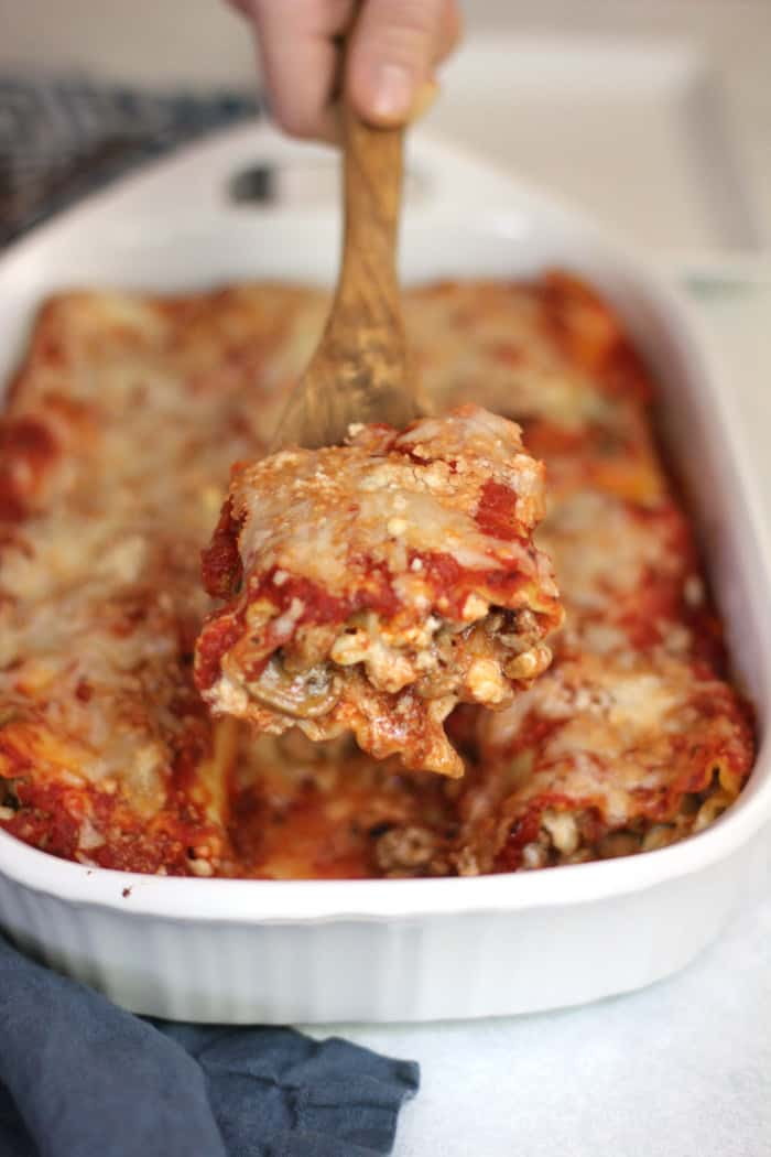 Side view of baked lasagna roll-ups, with a hand scooping out one serving with a wooden spoon.