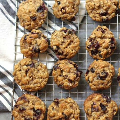 Overhead shot of Mini Cranberry Oatmeal Cookies on a wire cooling rack, with a gray and white napkin.