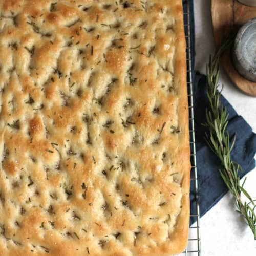 Overhead shot of rosemary focaccia bread on a wire cooling rack, with fresh rosemary beside it.