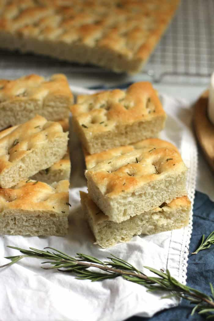 Side shot of rosemary focaccia bread sliced into rectangles, with a large chunk in background.