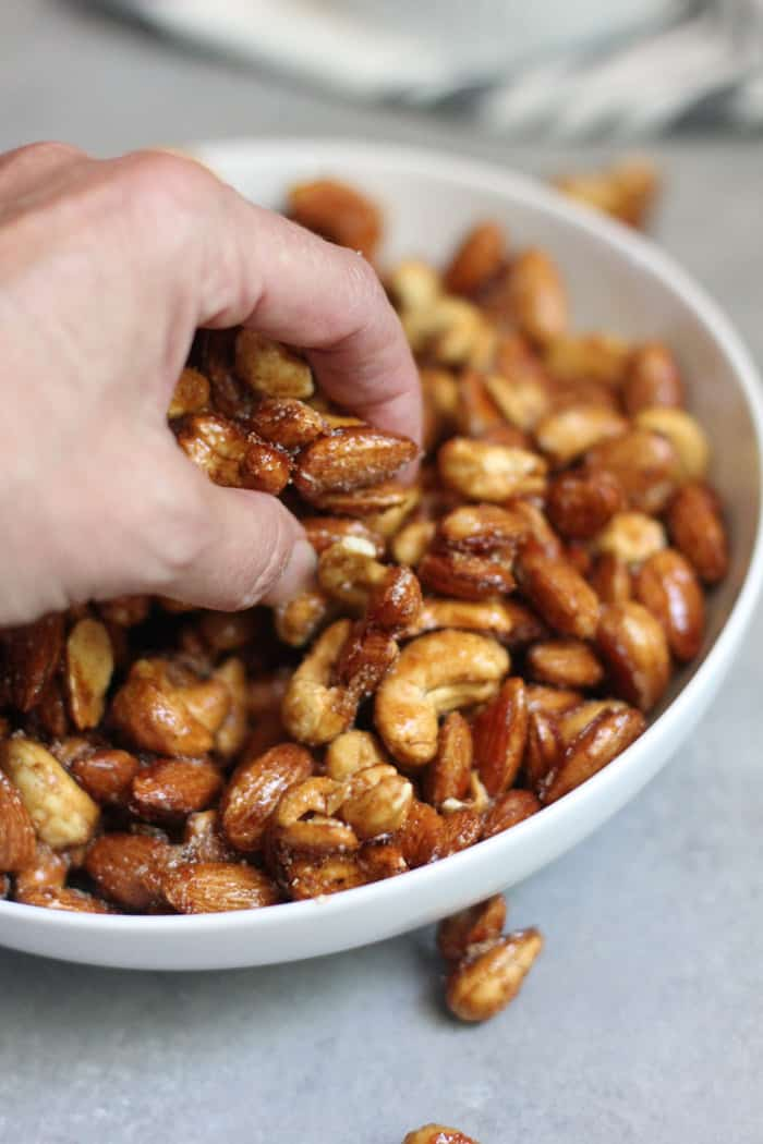 Side view of honey roasted nuts (cashews and almonds) in a white bowl with my hand reaching in for a handful.