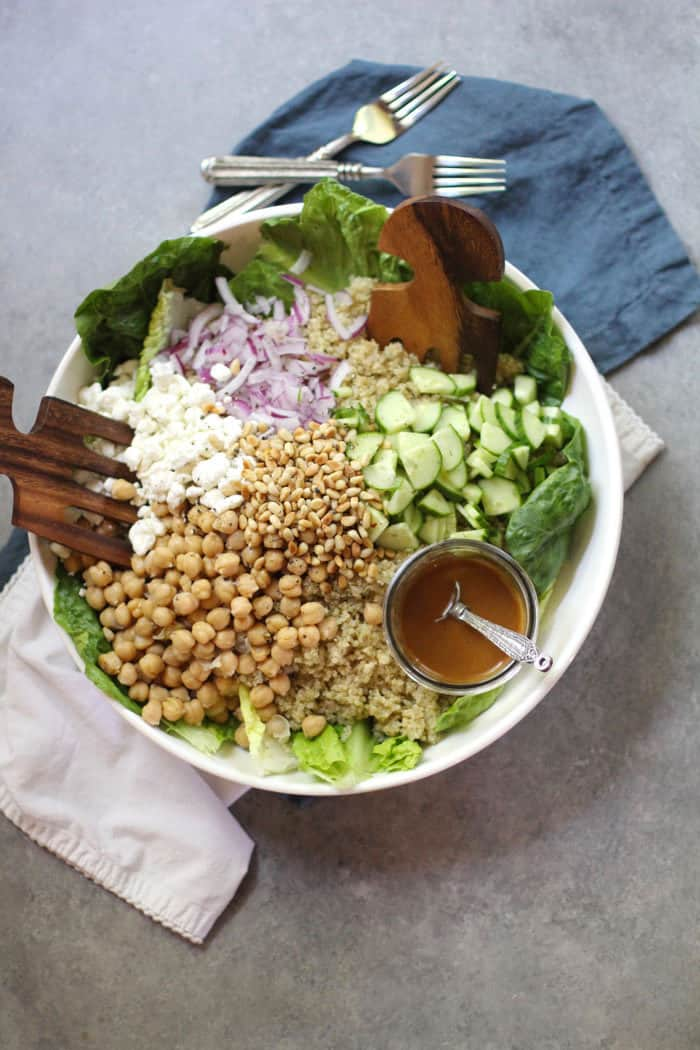 Overhead shot of a large white serving bowl, with the quinoa salad ingredients inside, separated in sections, with two wooden spoons on a gray background.