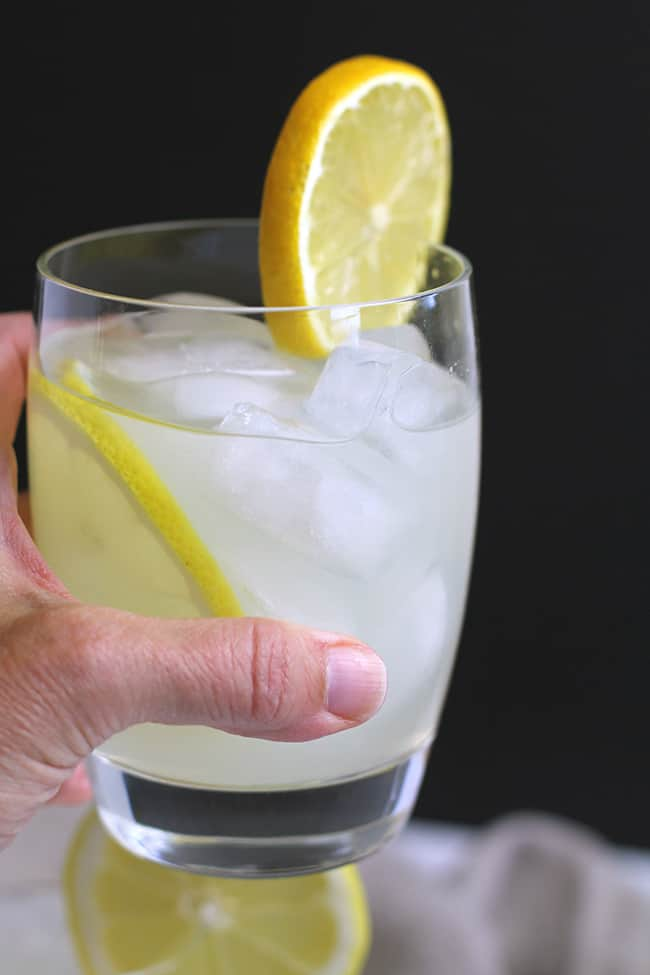 Side shot of a hand holding a limoncello moscow mule, against a black background.