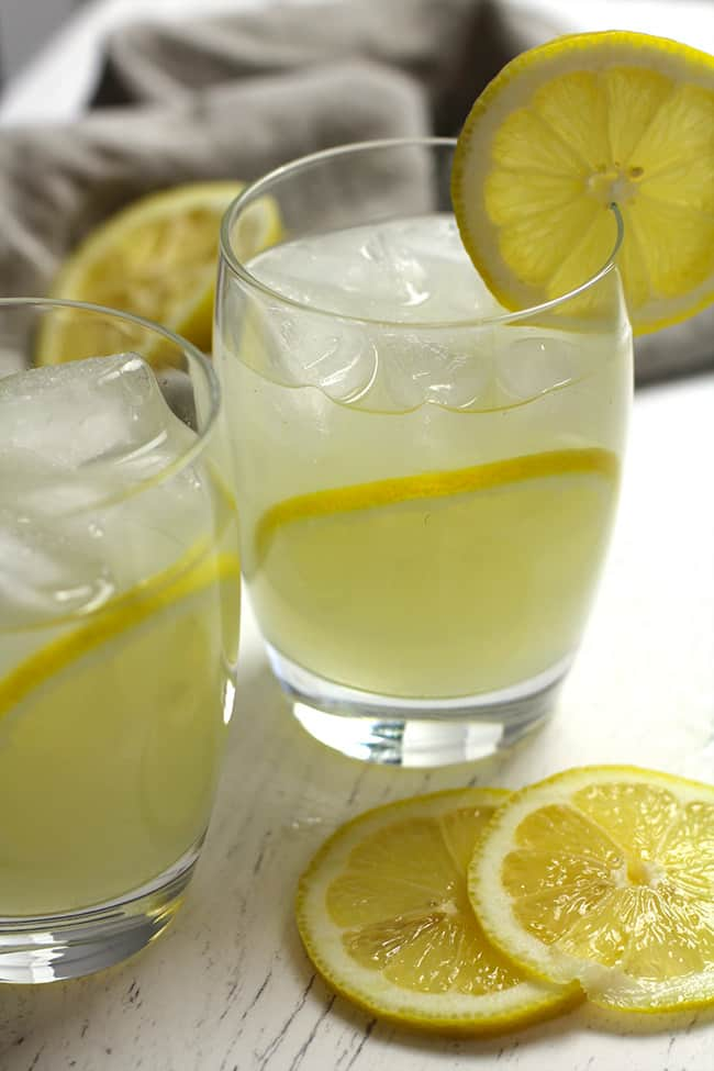 Side view of two Limoncello Moscow mules in clear glasses, with lemon slices.