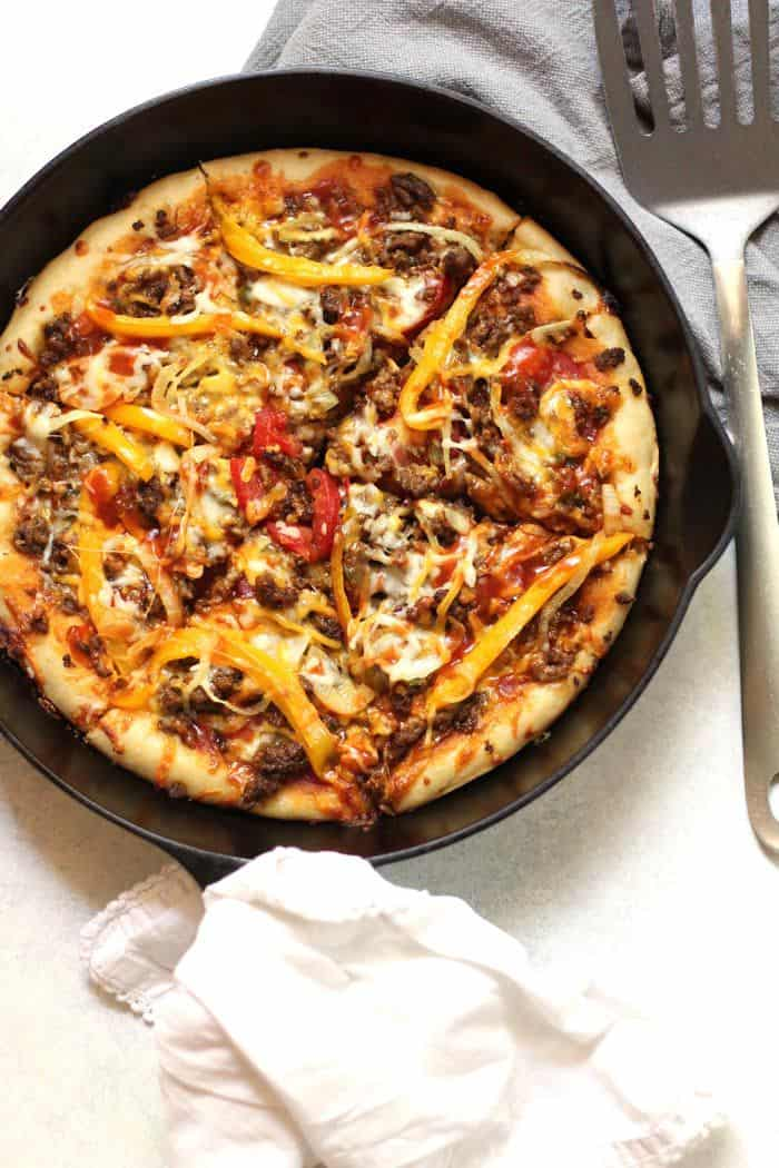 Overhead shot of taco pizza in a cast iron skillet, with a white napkin wrapped around the handle and a spatula beside it.