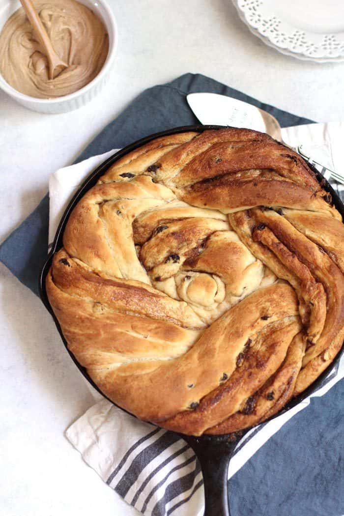 Overhead shot of a giant twist cinnamon raisin roll in a round cast iron skillet, on a blue napkin.