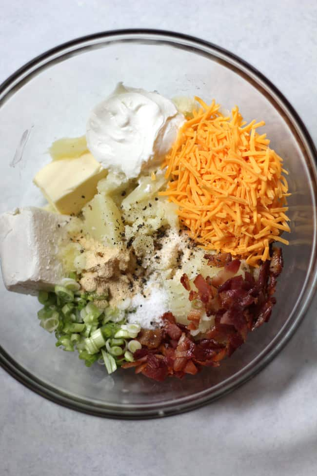 Overhead shot of twice baked potato ingredients, by ingredient in a glass bowl on a white background.