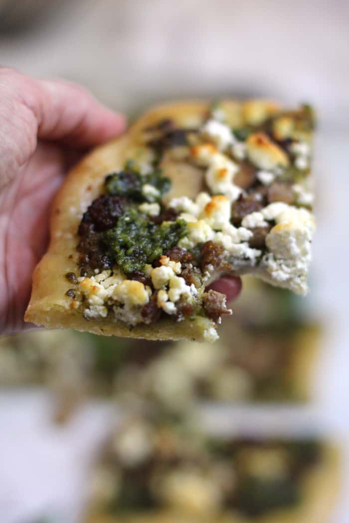 Close-up shot of my hand holding a slice of sausage and mushroom pesto flatbread, with a large bite out of it.