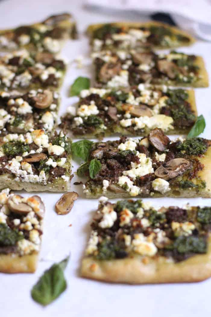 A side angle of sausage and mushroom pesto flatbread on white background, showing some close up pieces in focus.