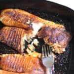 Two pieces of blackened tilapia in a skillet.
