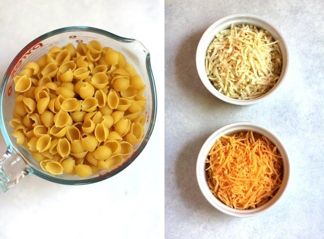 Overhead shot of 1) macaroni noodles in a measuring cup, and 2) white and cheddar cheese in two separate white bowls.