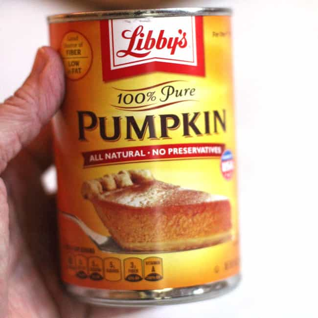 My hand holding a can of Libby's pure pumpkin.