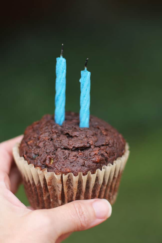 Close-up of my hand holding a chocolate zucchini muffin with two blue candles against a green background.
