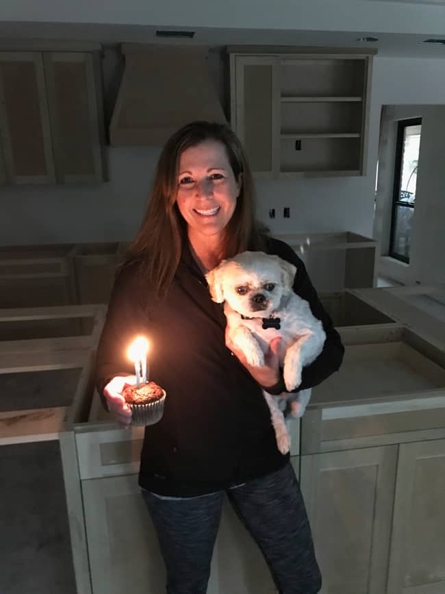 Picture of me holding my shih tzu pup and a chocolate cupcake with 2 candles, in front of my kitchen that is getting remodeled.
