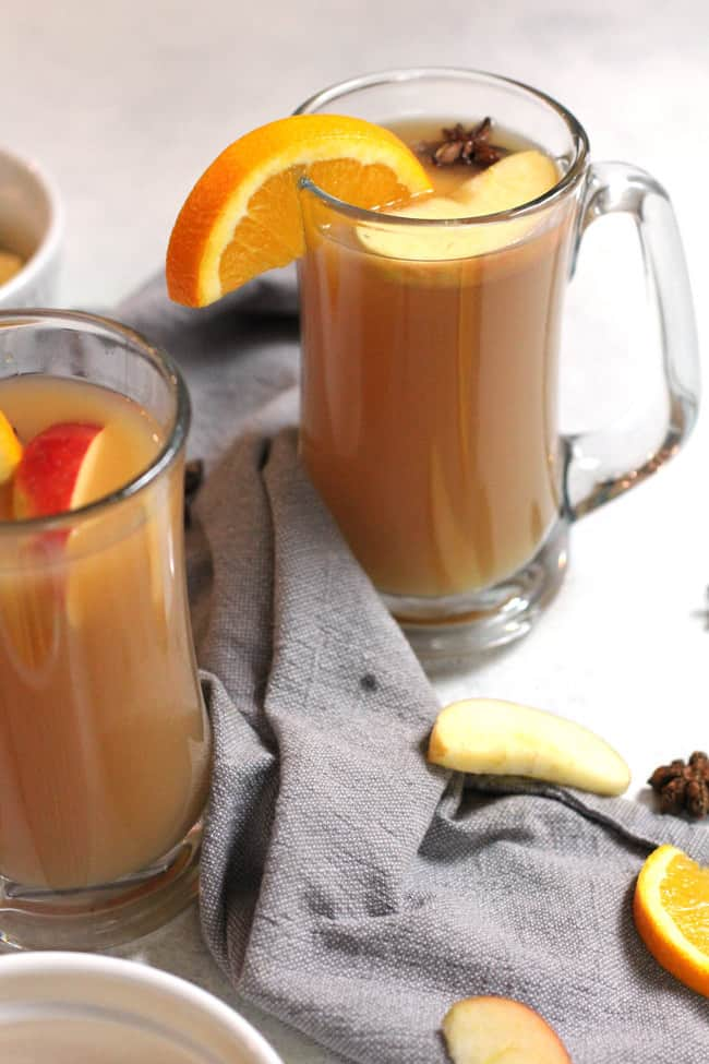 Side angle shot of mulled cider in large clear mugs, with orange slices and apple slices as garnish, on a white background with gray napkins.