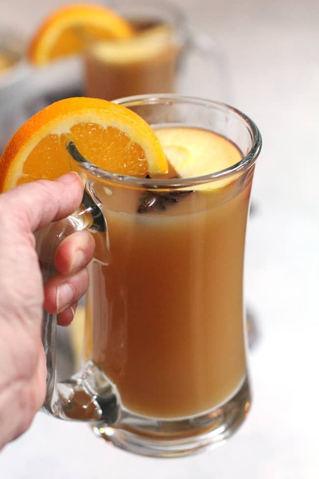 Side angle shot of my hand holding a mug of mulled cider, with orange slices and apple slices as garnish, on a white background with gray napkins.