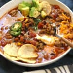 Side shot of Turkey Taco Soup, filled with toppings and a spoon, all on blue and white napkins.