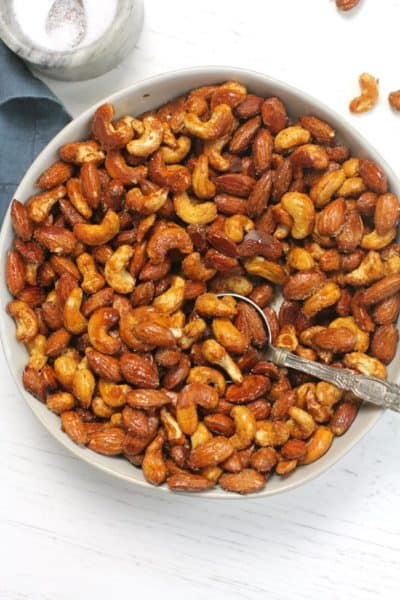 Overhead shot of a white bowl of honey roasted nuts, with a spoon inside, on a white background.