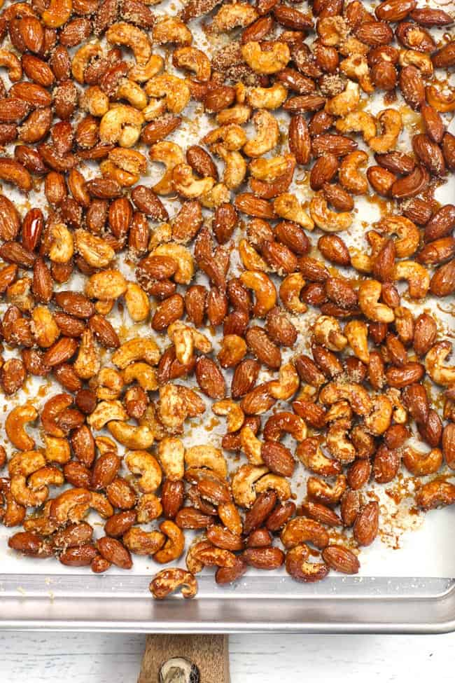 Overhead shot of a baking sheet covered with baked honey roasted nuts on white parchment paper.