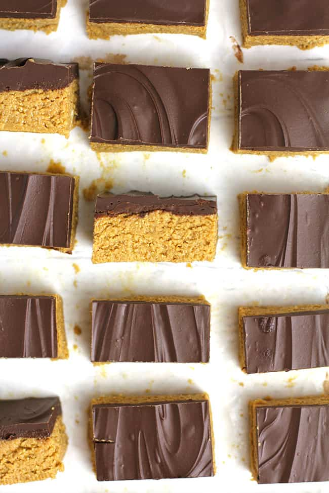 Overhead shot of sliced no bake peanut butter bars, with a few turned on their sides, on a white background.
