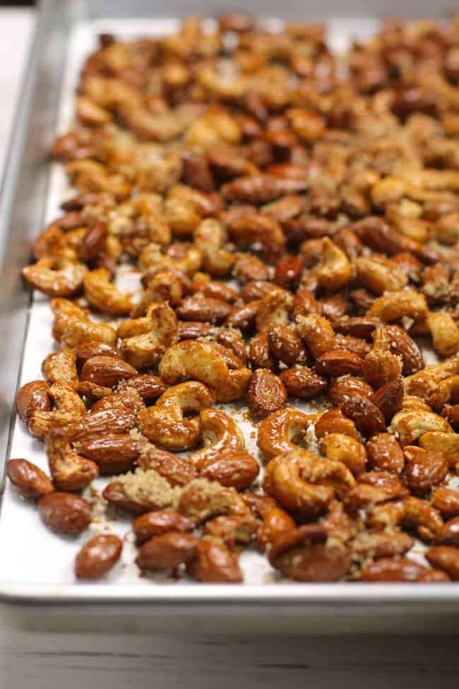 Side shot of a baking sheet of honey roasted nuts, on white parchment paper.