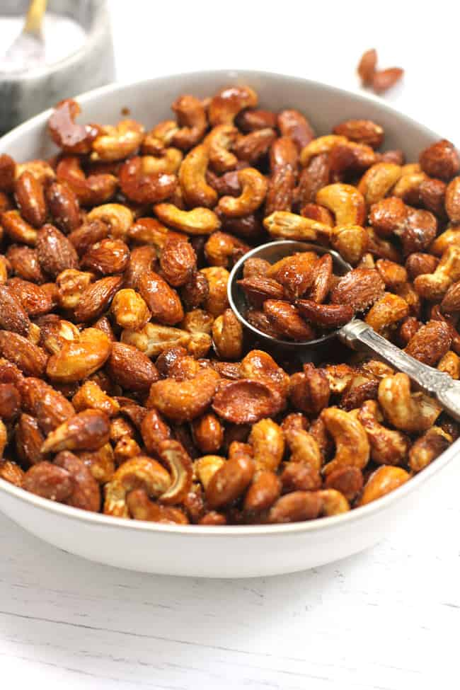 A white bowl of honey roasted nuts with a spoon inside.