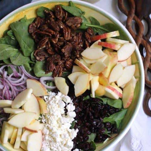 Overhead shot of a large bowl of Candied Pecan and Apple Holiday Salad, with the ingredients separated by type, along with wooden spoons and the vinaigrette in a mason jar.
