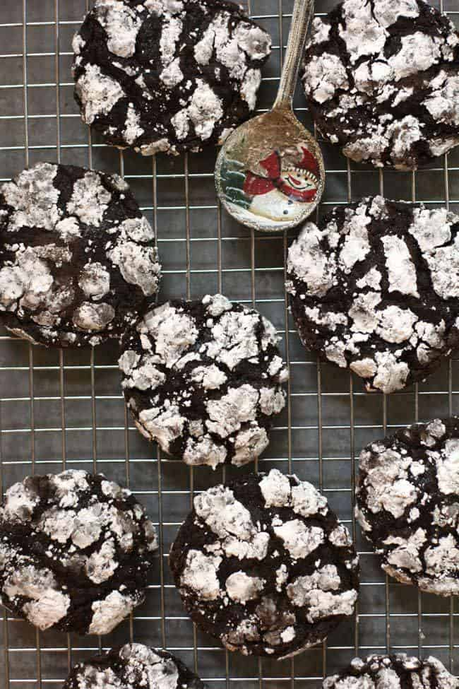 Overhead shot of chocolate crinkle cookies on a cooling rack, on a gray background.