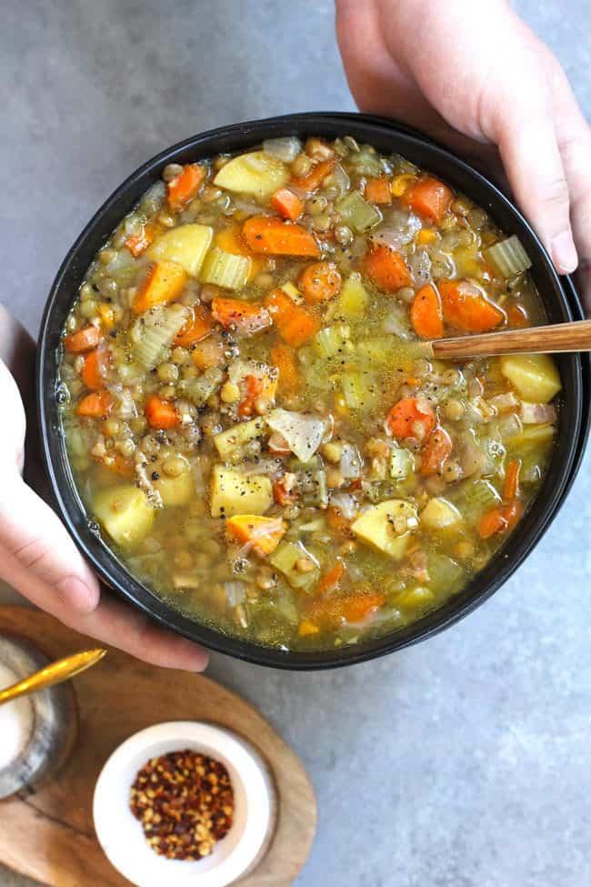 Overhead shot of hands holding a black bowl of detox lentil soup, over a gray background.