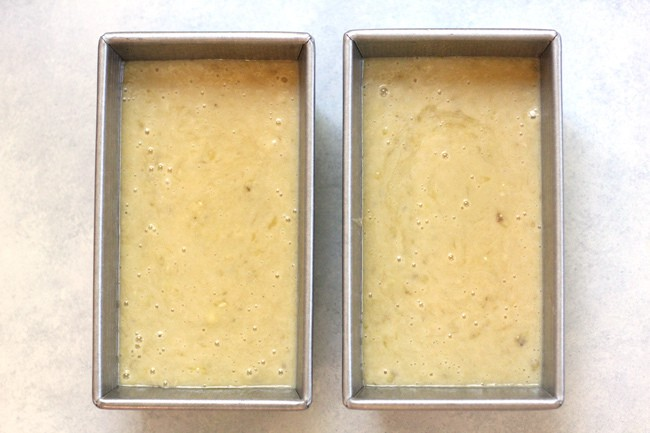 Overhead shot of two pans of banana bread batter, ready to go in the oven, on a white background.