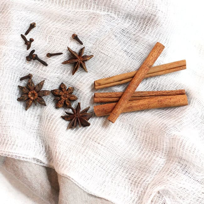 Overhead shot of cinnamon sticks, star anise, and whole cloves, on a white cheesecloth.