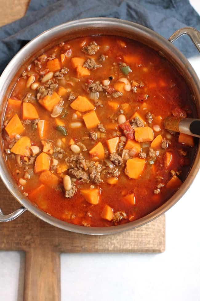 Overhead shot of a large stock pot of sweet potato turkey chili, on a wooden board with a blue napkin.