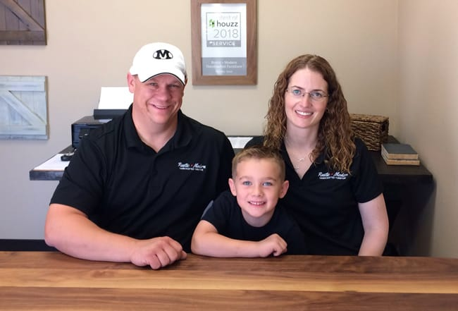 Picture of owners, Ken and Emily Williams and their son, sitting at a wood table in their office.