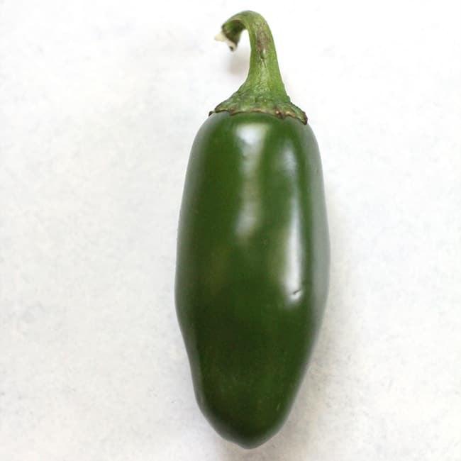 Picture of a green jalapeño on a white background.