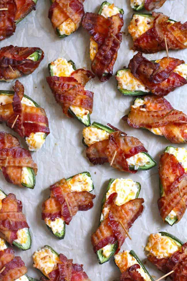 Overhead shot of just-baked bacon wrapped jalapeño poppers on a baking sheet with parchment paper.