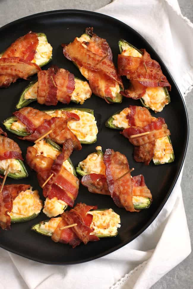 Overhead shot of bacon wrapped jalapeño poppers on a black plate, set on a white napkin.