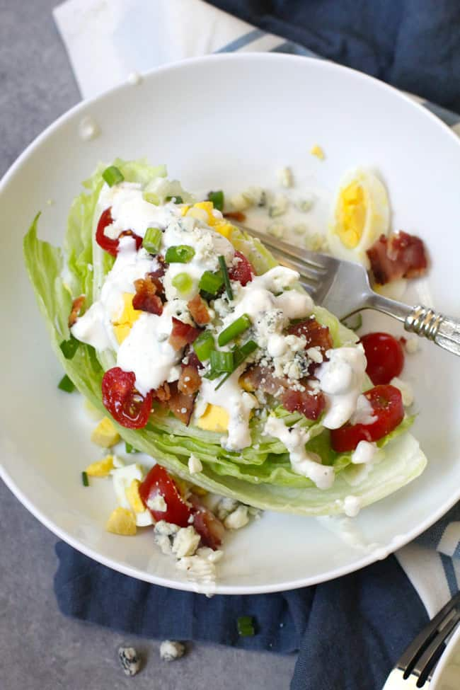Close-up shot of a white bowl of wedge salad with blue cheese dressing, on blue and white napkins.