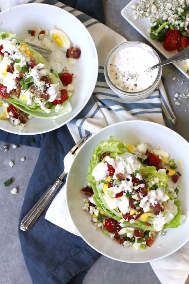 Overhead shot of two white bowls of wedge salad with blue cheese dressing, on blue and white napkins.