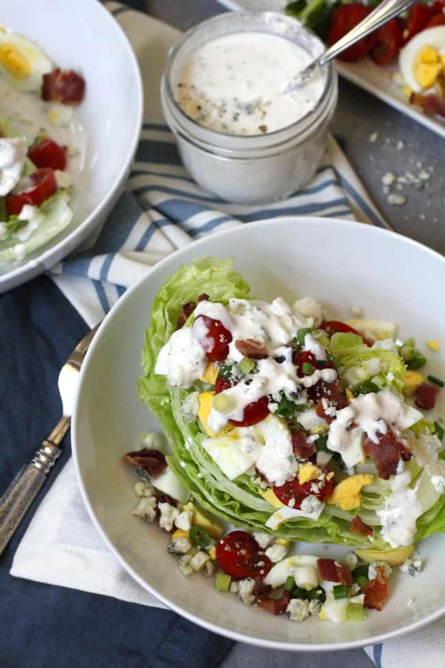 Overhead shot of a white bowl of wedge salad with blue cheese dressing, on blue and white napkins.