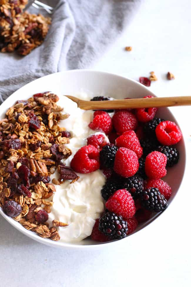Overhead shot of a white bowl, filled with granola, yogurt, and fresh berries, with a wooden spoon inside.