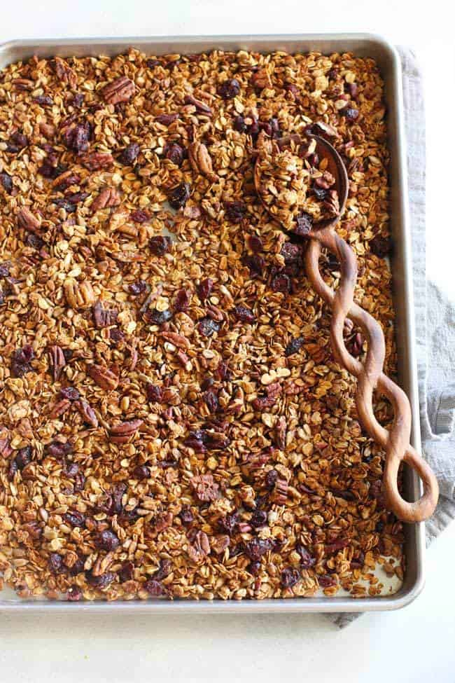 Overhead shot of a baking sheet full of granola, with a wooden spoon, on a gray napkin.
