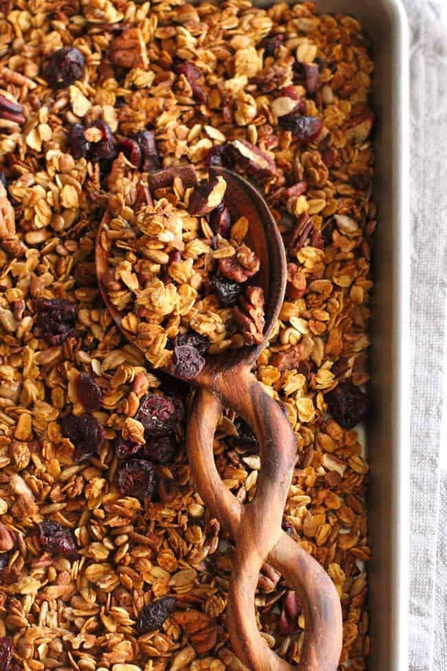 Close-up shot of granola on a baking sheet, with a wooden spoon scooping some.