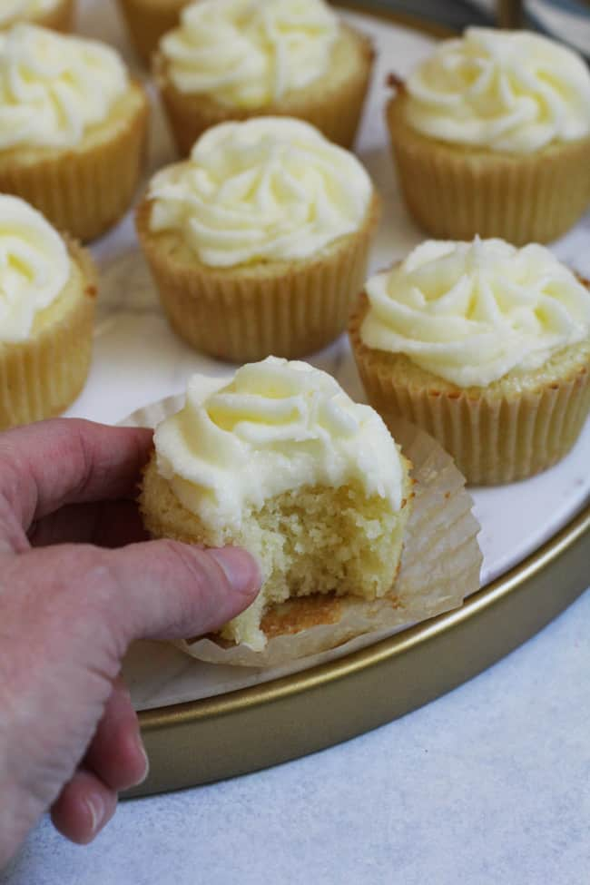 Side shot of my hand reaching for a lemon cupcake that has a bite out of it, on a white tray with other cupcakes.