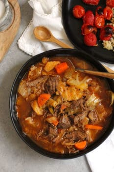 Overhead shot of Shredded Beef Cabbage Soup in a black bowl, with a plate of roasted tomatoes next to it.